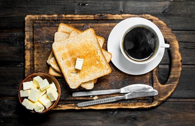 Geröstetes brot mit butter und kaffee. auf einer holzoberfläche.