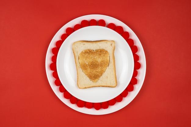 Geröstetes brot mit herzförmigem brand auf einem roten tisch. valentinstag urlaubskonzept. festliches frühstück, mittagessen.