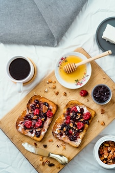 Geröstetes brot mit honig, frischkäse, marmelade mit roten früchten und kaffee