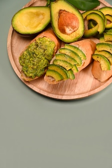 Geröstetes roggenbrot mit geschnittener avocado auf holzplatte.