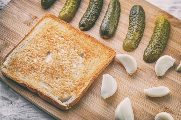 Geröstetes sandwich mit eingelegter gurke und frischem knoblauch auf einem holzschneidebrett