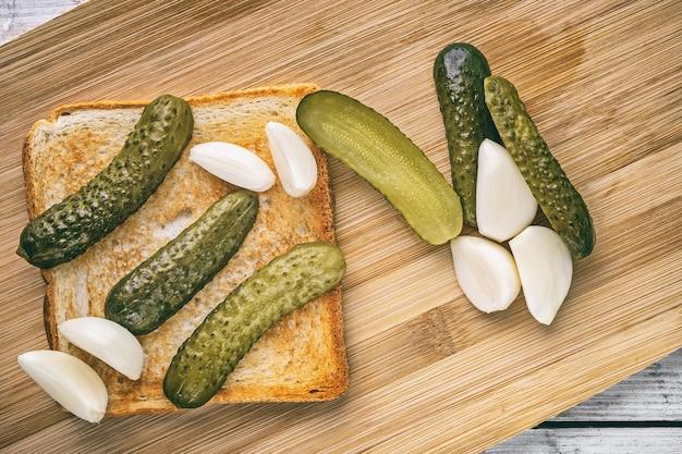 Geröstetes sandwich mit gurken und jungem frischem knoblauch auf einem holzschneidebrett