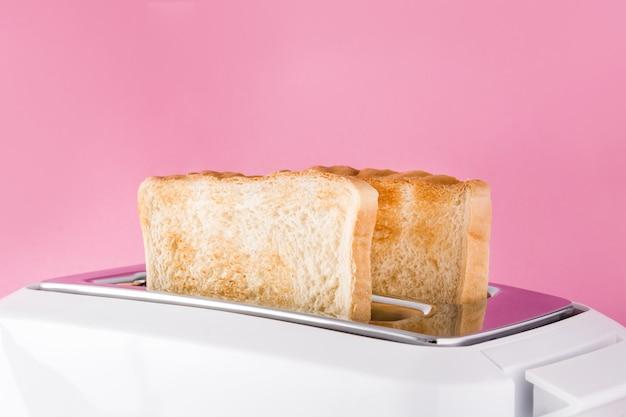 Geröstetes toastbrot im weißen toaster an der rosa wand