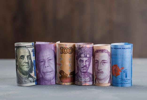 Gerollte banknoten auf gips und holztisch.