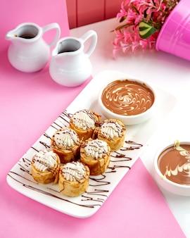 Gerollte crepes mit schokolade und schlagsahne auf teller