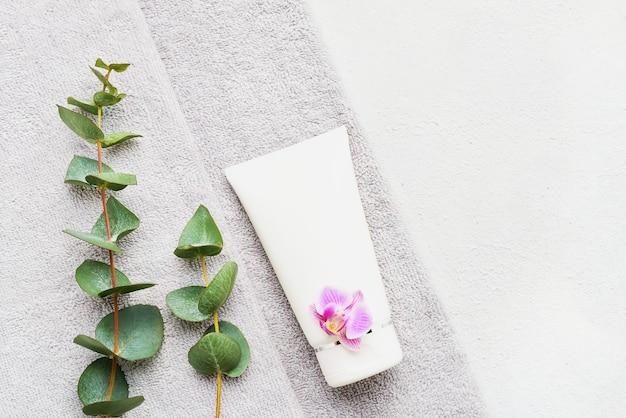 Gerollte graue handtücher, körperbehandlungsmodell und eukalyptuszweige auf weißem betontisch