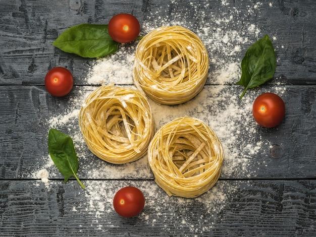 Gerollte nudeln, tomaten und spinatblätter auf einem holztisch. zutaten für die herstellung von nudeln.
