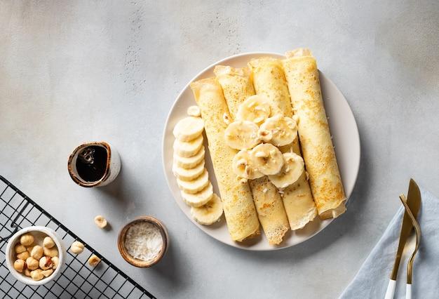 Gerollte pfannkuchen, crepes mit banane, nüssen, kokosnuss