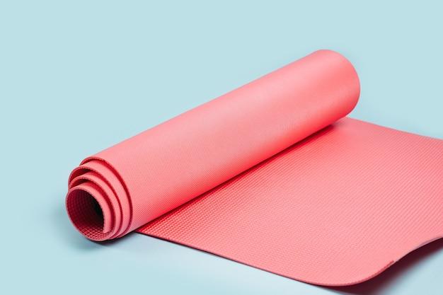 Gerollte rosa yogamatte auf blauem hintergrund. ausrüstung für yoga und meditation. gesundes lebensstilkonzept. heimtraining.
