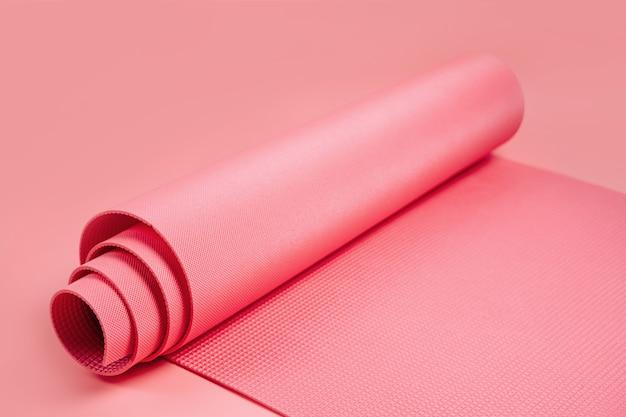 Gerollte yogamatte auf rosa hintergrund. ausrüstung für yoga und meditation. gesundes lebensstilkonzept. heimtraining.