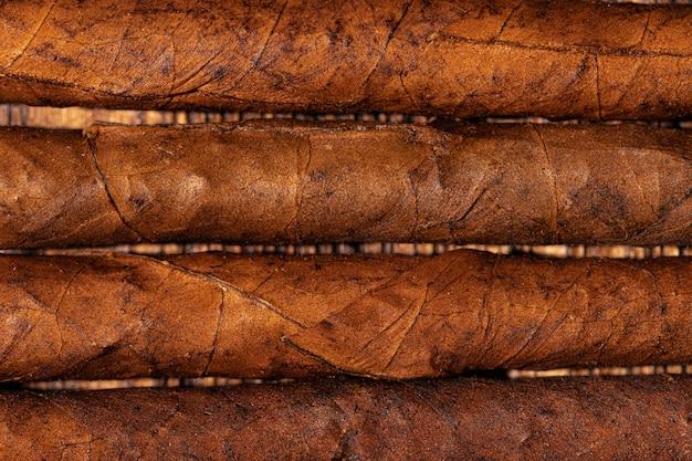 Gerollte zigarren in einer reihe auf hölzernem hintergrund