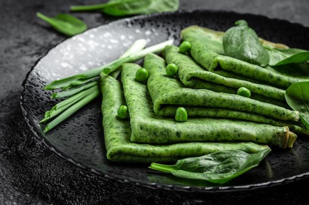 Gerollter dünner grüner pfannkuchen mit spinat und gemüse obenauf. hintergrund für lebensmittelrezepte. nahansicht.