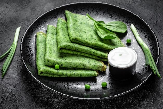 Gerollter dünner grüner pfannkuchen mit spinat und sauerrahm. hintergrund für lebensmittelrezepte. nahansicht.