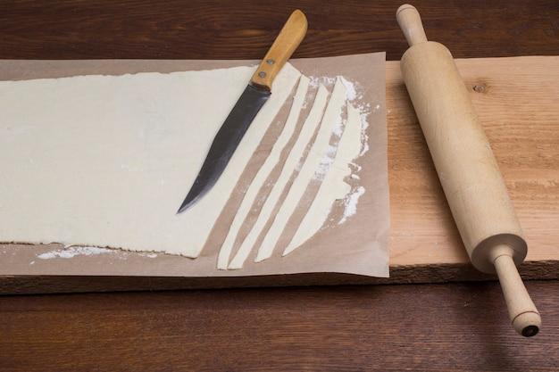 Gerollter teig, in streifen geschnitten. nudelholz, messer auf schneidebrett