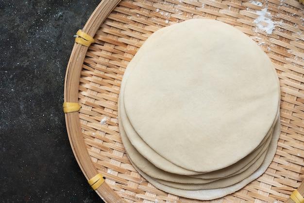 Gerollter ungekochter teig für indisches fladenbrot chapati auf bambusschale. kochfertiges konzept. einfache mahlzeiten. hausmannskost. draufsicht flat lay