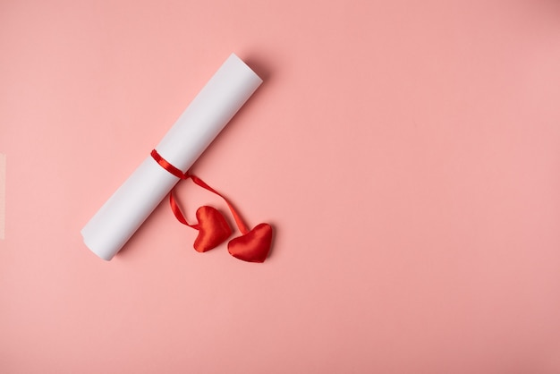Gerolltes blatt papier, gebunden mit einem roten band mit roten herzen. valentinstag konzept. flache lage, draufsicht.