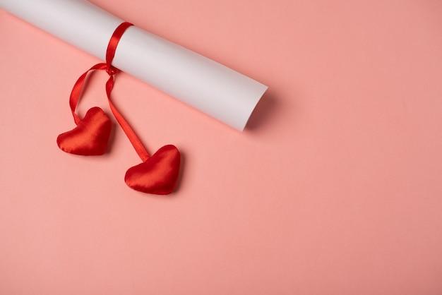 Gerolltes blatt papier mit dem roten band mit herzen gebunden. valentinstag konzept.