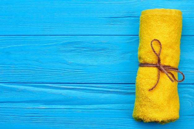 Gerolltes gelbes badezimmerfrotteetuch auf blauem hölzernem schreibtisch. vertikale aufnahme von oben.