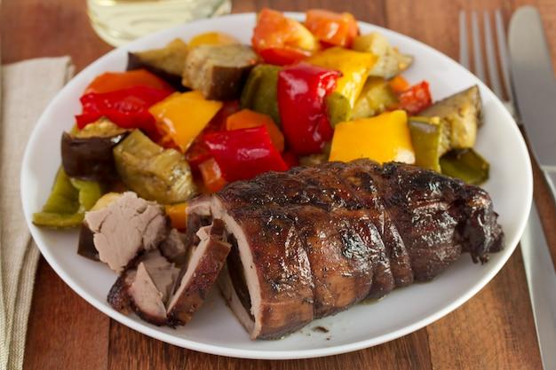 Gerolltes schweinefleisch mit wurst und gemüse