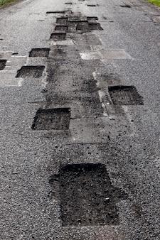 Gesägte quadratische und rechteckige öffnungen auf dem asphalt während reparaturen, restaurierung der alten fahrbahn, nahaufnahme