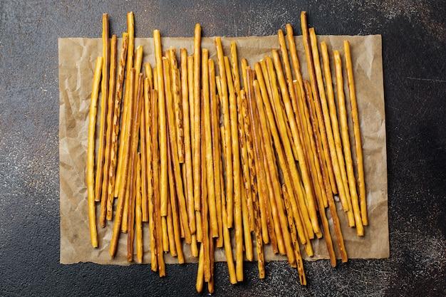 Gesalzene brotstangen oder lange knusprige salzbrezelstangen auf pergamentpapier auf altem braunem stein oder betontisch. draufsicht.