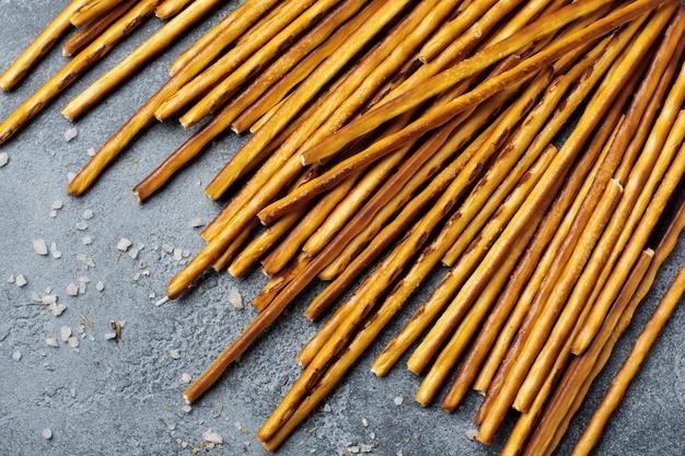 Gesalzene brotstangen oder lange knusprige salzbrezelstangen auf pergamentpapier auf altem grauem stein oder betontisch. draufsicht.