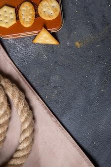 Gesalzene cracker der oberen entfernten ansicht mit seilen auf dem knusper-crackersnackfoto des grauen hintergrunds