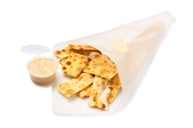 Gesalzene cracker in einer papiertüte und sauce in der plastikverpackung