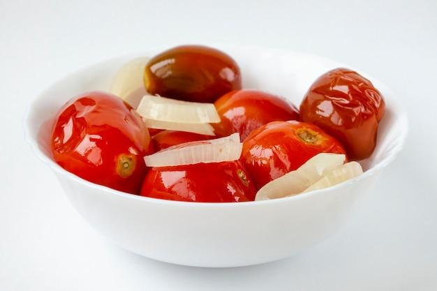 Gesalzene eingelegte tomaten mit zwiebeln in einem weißen teller