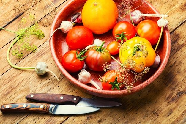 Gesalzene frische tomaten auf holzhintergrund. kochprozess, tomaten in dosen. eingelegtes gemüse, konserviert