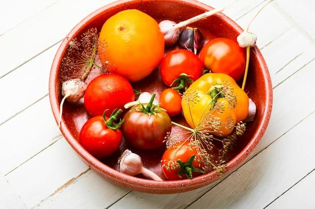 Gesalzene frische tomaten. kochprozess, tomaten in dosen. eingelegtes gemüse, konserviert auf weißem hintergrund