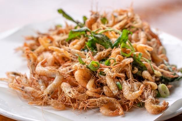 Gesalzene gebratene knusprige flussgarnelengarnele macrobrachium nipponese in einem weißen teller auf holztisch köstlichen taiwanesischen streetfood-lebensstil