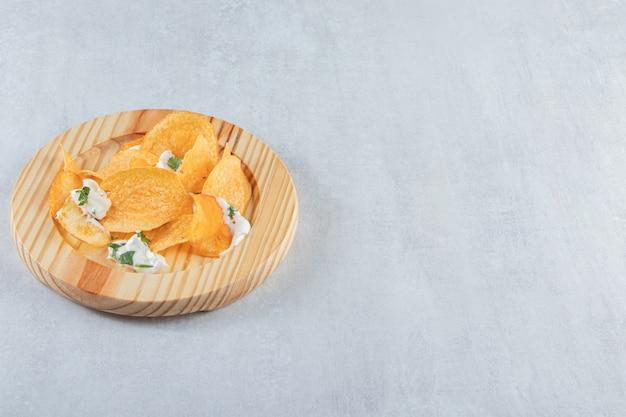 Gesalzene knusprige chips und frischer joghurt auf holzplatte.