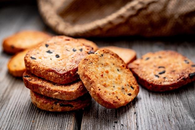 Gesalzene knusprige cracker mit sesam und sonnenblumenkernen auf altem küchentisch. gesundes essen