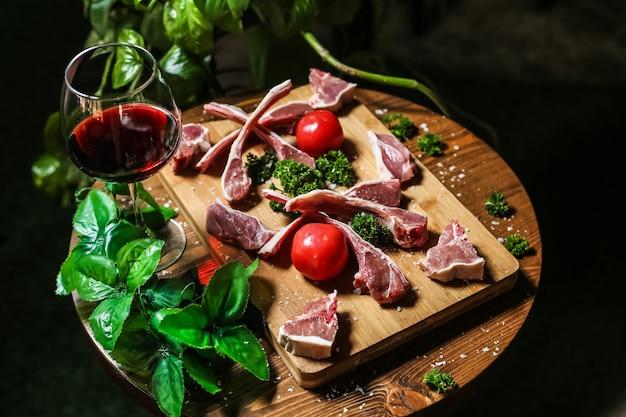 Gesalzene lammrippen, die zum kochen der tomaten-paprika-grün-rotwein-seitenansicht vorbereitet werden