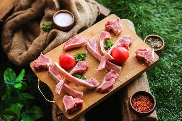 Gesalzene lammrippen zum kochen von tomaten-paprika-grünseitenansicht vorbereitet