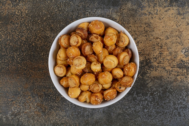 Gesalzene leckere cracker in weißer schüssel.