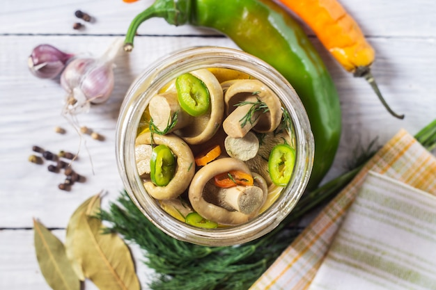 Gesalzene milchpilze oder eingelegte milchpilze in einem glas und zutaten, pfeffer, knoblauch, dill und lorbeerblatt