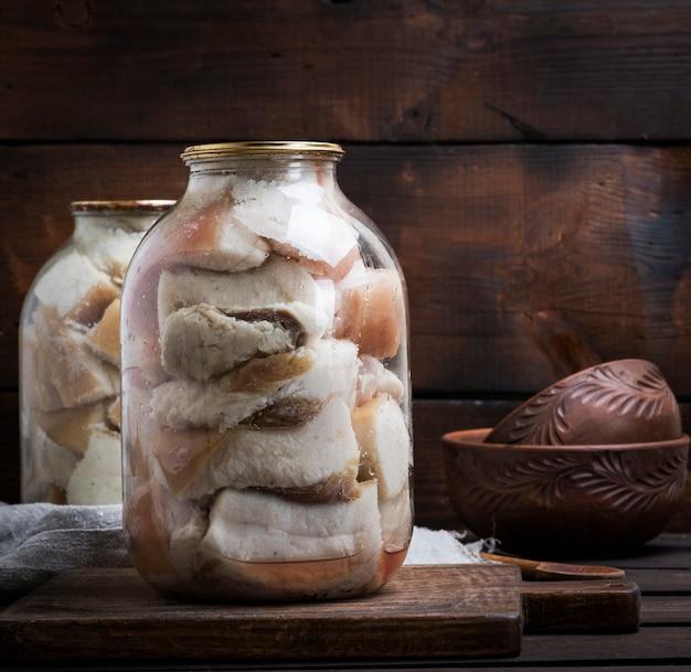 Gesalzene schmalzstücke mit fleisch werden in gläsern verschlossen