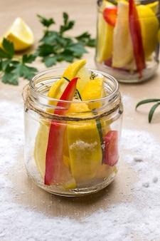 Gesalzene zitronen in dosen und chilischoten im glas. fermentierende lebensmittel. leichte oberfläche