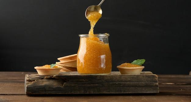 Gesalzener hechtkaviar in einem glas auf einem holzbrett