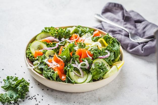 Gesalzener lachs (forelle) und kohlsalat in einer weißen platte auf einem weißen hintergrund.