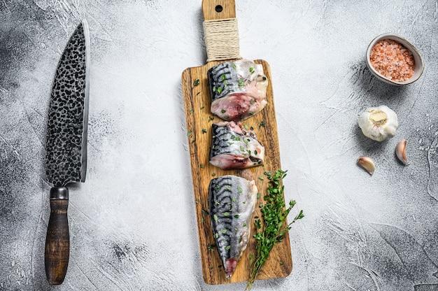Gesalzener makrelenfisch in scheiben auf einem holzbrett. weißer hintergrund. ansicht von oben.