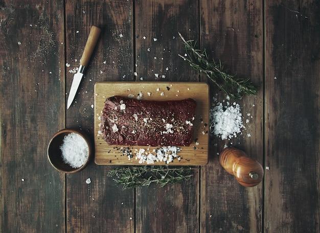 Gesalzenes, gepfeffertes stück fleisch, bereit zum grillen auf einem holztisch zwischen kräutern und gewürzen auf holz