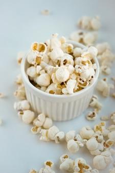 Gesalzenes popcorn im weißen tontopf mit verstreutem popcorn