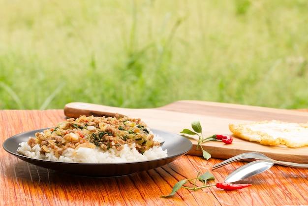 Gesalzenes schweinefleisch mit paprika- u. basilikumblättern im schwarzblech auf hölzerner tabelle