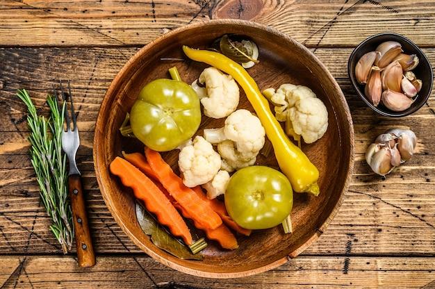 Gesalzenes und eingelegtes gemüse in einem holzteller aufbewahren