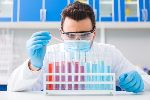 Gesamtkonzentration. brunette professioneller männlicher laborator, der mit pipette arbeitet, um flüssigkeit in fläschchen fallen zu lassen, während sie in stand stehen