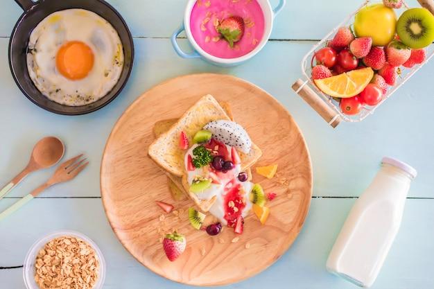 Gesamtmilchjoghurt des toasts und der frucht mit spiegelei in einer bratpfanne auf holz