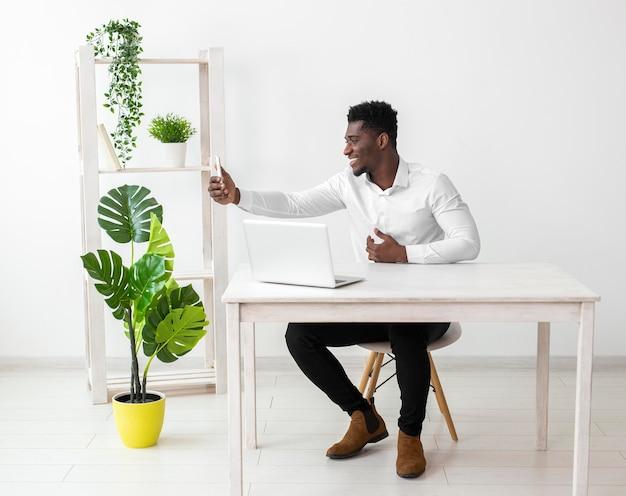 Geschäft afroamerikaner mann, der sein telefon für ein foto hält